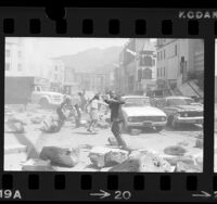 """Actors dodging rubble during filming of motion picture """"Earthquake"""" in Los Angeles, Calif., 1974"""