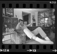 Actor Rock Hudson lounging on couch at his home in Los Angeles, Calif., 1974
