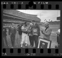 Hank Aaron receiving honors from Tom Bradley, Ernest Debs and John Ferraro before Braves vs Dodgers game, Calif., 1974