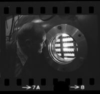 Physicist Kenneth R. Mackenzie looking into plasma chamber at UCLA, Calif., 1974