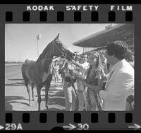 Tennis player Chris Evert meeting her namesake race horse at Hollywood Park, Calif., 1975