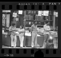Four people waiting at bus stop as Richard Nixon's resignation address plays on television in electronics store behind them, Los Angeles, Calif., 1974