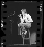 David Bowie, seated on stool during performance at the Universal Amphitheater in Los Angeles, Calif., 1974
