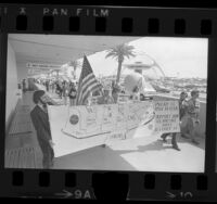 "Pan American Airways employees carrying banner reading ""Pan AM is Made in USA Support Our U.S. Airline.."" during demonstration at LAX, Calif., 1974"