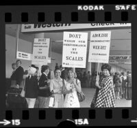 """Western Airlines flight attendants with signs reading """"Don't Weigh Our Performance by the Scales"""" picketing ticket counter in Los Angeles, Calif., 1974"""