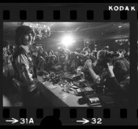 Musician George Harrison standing before crowd of photographers in Los Angeles, Calif., 1974