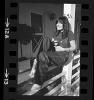 Singer Linda Ronstadt reclining on porch railing in Los Angeles, Calif., 1974
