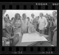 Joanne Woodward with other actors signing petition against oil drilling off the California coast in Santa Monica, Calif., 1974