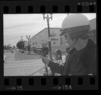 Police officer Dennis L. Mooneyham demonstrating handheld radar speedgun in Los Angeles, Calif., 1975