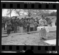 Buddhist priest Tri Sanh leading Vietnamese refugees in prayer at Camp Pendleton, Calif., 1975