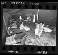 Vietnamese mother and children in tent at refugee camp at Camp Pendleton, Calif., 1975