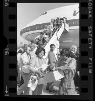 South Vietnamese and Cambodian orphaned infants being carried in cardboard boxes off plane at Los Angeles International Airport, Calif., 1975