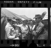 Former South Vietnamese Premier Nguyen Cao Ky talking with other refugees at Camp Pendleton, Calif., 1975