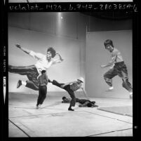 Four men performing karate before backdrops with images of Bruce Lee during audition for movie in Los Angeles, Calif., 1975