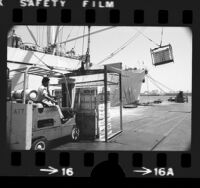Longshoreman loading boxes of Sunkist Lemons onto ship in Long Beach, Calif., 1975
