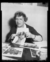 Anthropologist Margaret Mead displaying photographs of African people during visit to Los Angeles, Calif., 1954