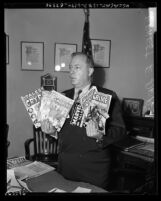 City councilman Ernest Debs holding horror comic books that were purchased in his district in Los Angeles, 1954