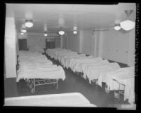 Bodies on gurneys, covered in white sheets at Los Angeles County Morgue, Calif., 1954