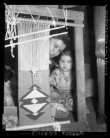 Woman at loom with child at the Los Angeles Indian Center 2920 Beverly Blvd. in Los Angeles, Calif., 1954