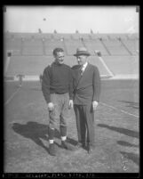 Football player Red Grange in uniform and sports promoter C. C. Pyles at Los Angeles Memorial Coliseum, 1923