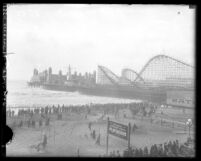 Roller coaster and buildings along pier with beach goers on shoreline of beach of on Santa Monica Pier, Santa Monica, circa 1923