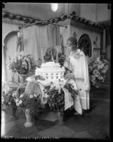 Aimee Semple McPherson surrounded by flowers, cutting into Angelus Temple cake