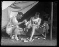 "Two runners caring for their feet during a break in C. C. Pyle's Route 66 cross country footrace called the ""Bunion Derby,"" 1928"