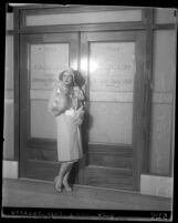 Motion picture actress Clara Bow posing in front of Los Angeles Grand Jury room doors, 1930