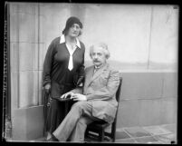 Portrait of scientist Albert Einstein seated, with his wife Elsa standing next to him, circa 1931