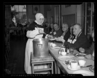 Nun of Little Sisters of the Poor serving Thanksgiving Day meal to group of men in Los Angeles, Calif., 1939