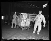 Two longshoremen hauling wooden crates at Los Angeles Harbor; San Pedro, 1939