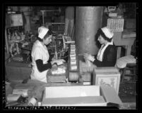 Two women packaging butter at State Relief Administration cooperative in Los Angeles, circa 1940