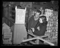 Couple in grocery store reading food stamps poster in Los Angeles, circa 1940