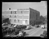 Long line of people standing outside Los Angeles Department of Motor Vehicles building waiting for 1940 automobile licenses, 1940
