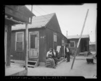 Couple sitting besides a California State Emergency Relief Administration plank board house, circa 1935