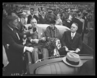 President Franklin D. Roosevelt and wife Eleanor seated in open car talking to reporters on visit to Los Angeles, Calif., 1935