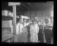 People lined up at counter of Los Angeles County Welfare Food Exchange, circa 1934