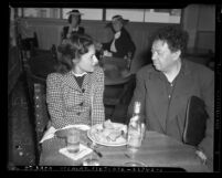 Artist Diego Rivera seated at restaurant table with actress Paulette Goddard, circa 1940