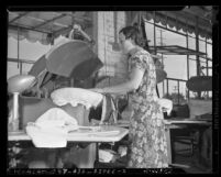 Woman operating press iron in a cleaning and dyeing shop in Los Angeles, Calif., circa 1940