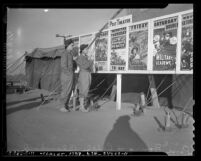 Soldiers Rene Bourg and Ralph Blanchard looking at movie posters in Fort Ord, Calif., 1940
