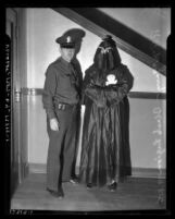 Los Angeles Police officer R. F. McGarry standing with person in Black Legion hood and robes, circa 1936
