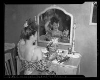 Actress Carmen Miranda at dressing table with her fruit hat, Los Angeles, Calif., circa 1941