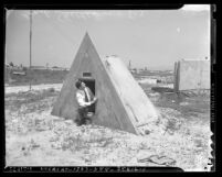 Man sitting in doorway of concrete, triangle shaped bomb shelter in Los Angeles, Calif., circa 1941