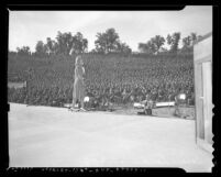 Actress Carole Landis performing before crowd of Army soldiers at Fort Hunter Liggett, Calif. during 1941 Hollywood stars show