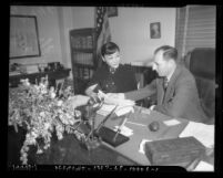 Actress Anna May Wong sitting at desk with Los Angeles District Attorney Buron Fitts reviewing extortion letters, Los Angeles, 1937