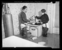 Couple wearing waders, cooking at stove in flooded kitchen, 1937 flood Long Beach, Calif.