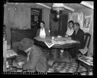 Three Japanese Americans sitting at table, as forth person examines a book in their Terminal Island, Calif. home, circa 1942