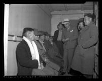 Officer questioning Japanese American men during raids carried out in Los Angeles County, Calif., 1942