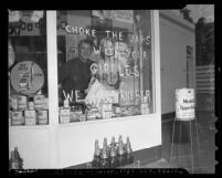 """Man looking out a gas station window upon which is written """"CHOKE THE JAPS WITH YOUR GIRDLES WE WANT RUBBER"""" in 1942, Los Angeles, Calif."""