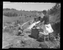 Homeless Mrs. John Groves and family preparing meal on open cookstove at camp setup on hillside in Los Angeles, Calif., 1948